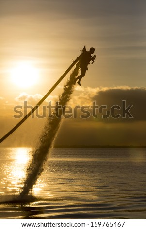 Cancun, Mexico - Oct 16, 2013:  A unidentified man using a water powered jetpack in Cancun, Mexico on Oct 16, 2013. - stock photo