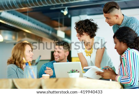 Candid image of a group with succesful business people caught in an animated brainstorming meeting - stock photo