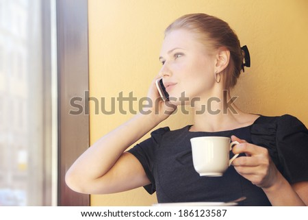 Candid image of a young woman talking on the phone in a cafe. - stock photo