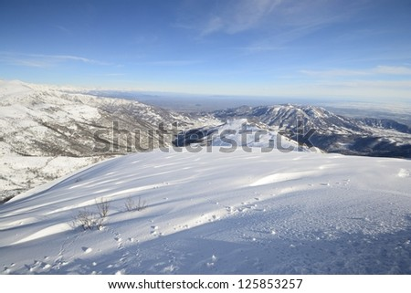Candid off-piste ski slope in powder snow and scenic alpine background - stock photo