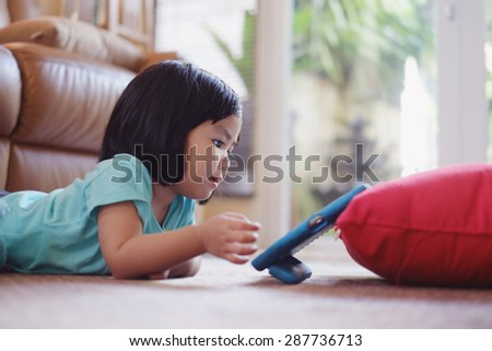 Candid picture of baby girl watching video on tablet  - stock photo