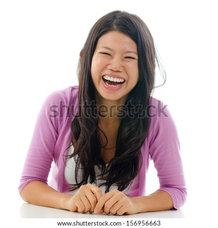 Candid portrait Asian woman laughing with mouth opened big. Sitting isolated on white background. - stock photo