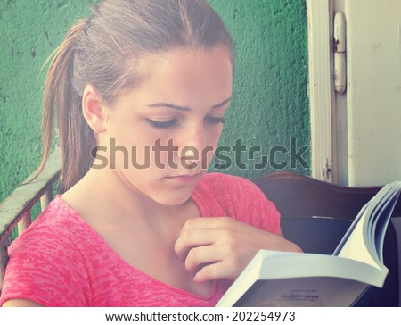 Candid portrait of a pretty teenage girl reading  a book on the balcony - stock photo
