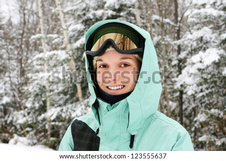 Candid portrait of a young caucasian woman wearing sky apparels enjoying the great outdoors or nature on a cold winter day. - stock photo