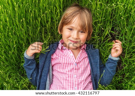 Candid portrait of adorable little boy of 4-5 years old, wearing pink shirt and blue jacket, playing alone outdoors, laying on grass - stock photo