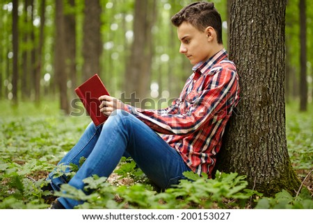 Candid shot of a teen boy reading a book in the forest - stock photo