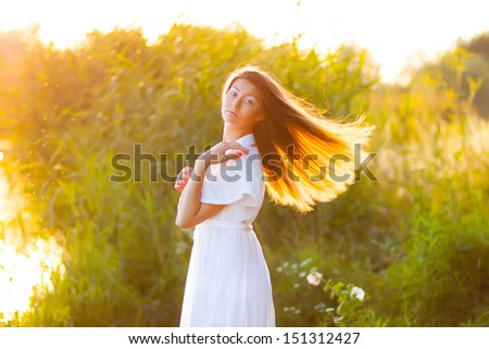 Candid skipping carefree adorable woman with long hair in field at summer sunset. - stock photo