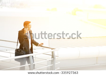 Candid young Asian Indian businessman on the phone at outdoor office building. India male business man, sunset light at background. - stock photo