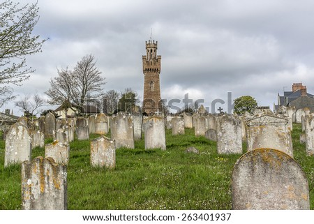 Candie Road Cemetery, not far from the Victoria Tower. Victoria Tower - famous monument in Saint Peter Port, Guernsey, erected in honor of visit by Queen Victoria and Prince Albert to island in 1846. - stock photo