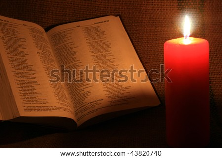 candle and book in darkness - stock photo