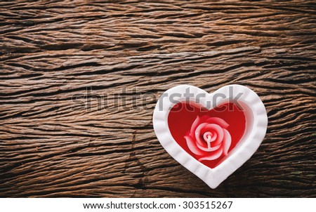 Candle aroma in white heart for the spa on wooden background in vintage style soft focus. - stock photo
