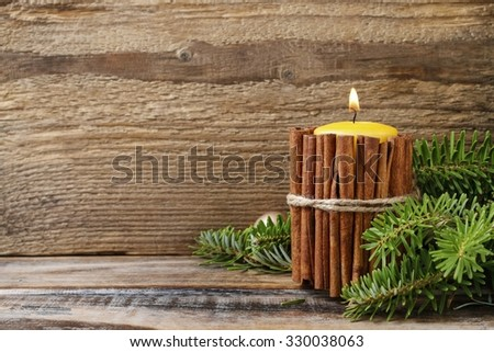 Candle decorated with cinnamon sticks, christmas decoration - stock photo