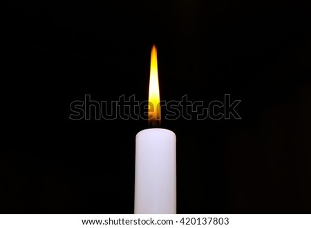 Candle flame closeup isolated on black background. Design element for memory day card, cover. - stock photo
