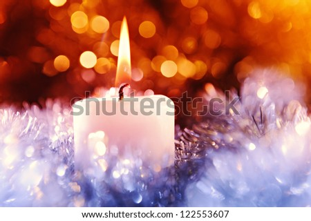 Candle in a christmas decoration and defocused lights - stock photo
