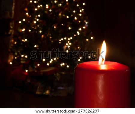 Candle in front of a Christmas tree that is lit - stock photo