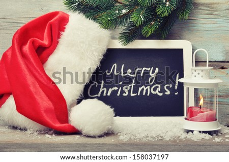 Candle in lantern and framed blackboard with Santa's hat on wooden background - stock photo