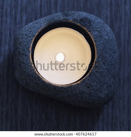 Candle in stone from above, lunar light, square image - stock photo