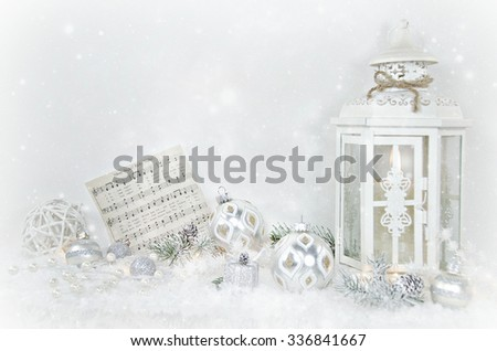 candle in white lantern with holiday ornaments in snow - stock photo