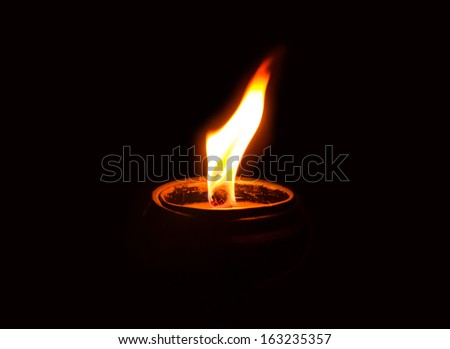Candle light  on the candlestick in the dark . - stock photo