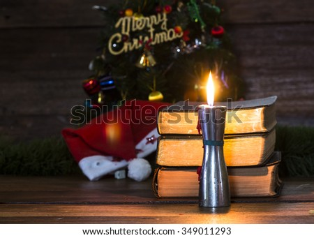 Candle light on wooden table against  holy bibles over wooden wall as a background, Christian concept - stock photo