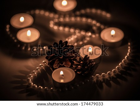 Candlelight and pearls with two cones - stock photo