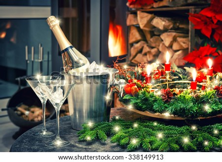 Candlelight dinner. Festive christmas and new year decoration with bottle of champagne and fireplace. Retro style toned picture - stock photo