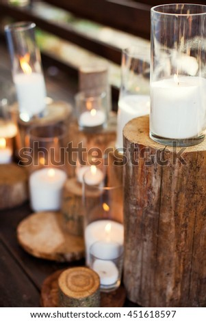 candles in glass vases on stumps - stock photo