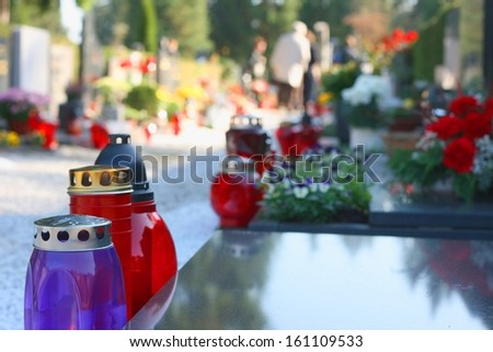 Candles on a grave on a sunny day, people in background - stock photo