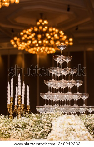 Candles on golden holders and champagne glasses in pyramid shape at the wedding with bokeh from chandelier - stock photo