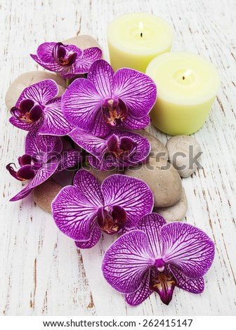 Candles, orchids and massage stones on a wooden background - stock photo