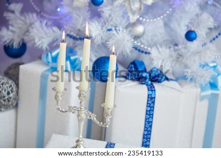 candlestick, three long candles, white Christmas tree with blue toys, garlands, beads, boxes, gifts - stock photo