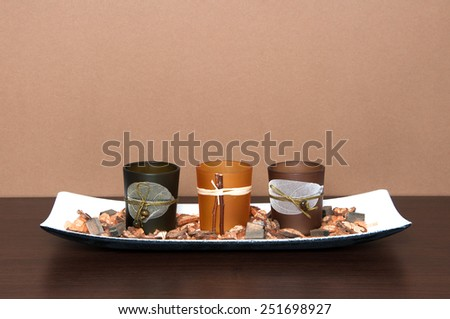 Candlesticks and other decorations for home interior on wooden table - stock photo