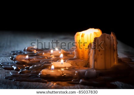 Candls with golden fire on shelf - stock photo