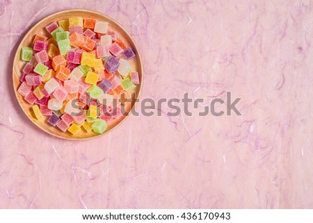Candy and jelly colorful in wooden dish on pink background - stock photo