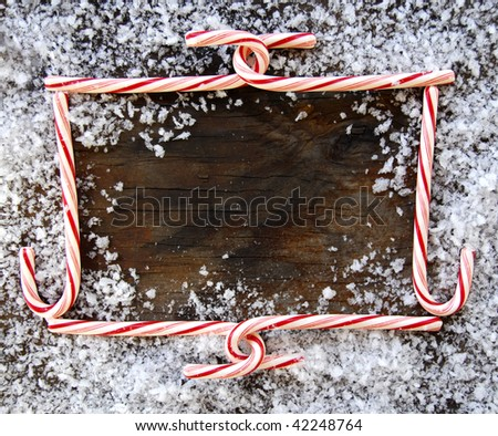 Candy Cane Christmas Frame on worn wood, surrounded by snow - stock photo