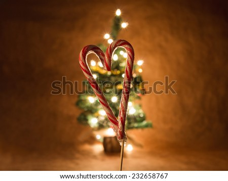candy cane heart shape with tree decorated in background with a shallow depth of field on the candy cane - stock photo