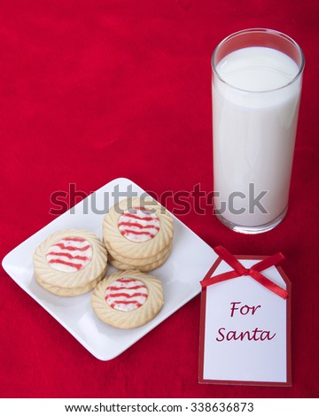 candy cane stripped peppermint flavor sugar cookies on a plate with a glass of milk. Note message tag says for santa - stock photo