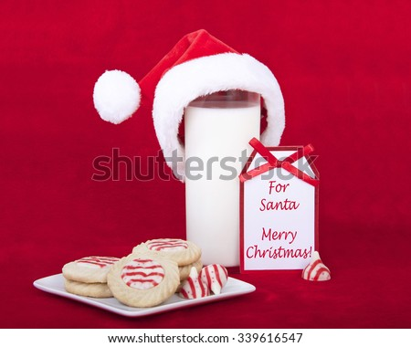 candy cane stripped peppermint flavor sugar cookies on a serving plate with a glass of milk and a miniature santa hat. Not card says For Santa Merry Christmas. - stock photo