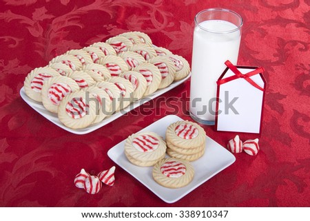 candy cane stripped peppermint flavor sugar cookies on a serving plate with cookies on a square plate for santa with a glass of milk. Note next to milk blank for your message - stock photo