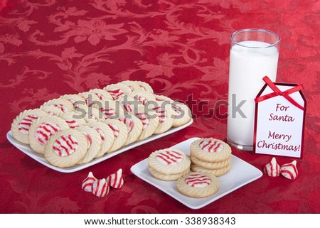 candy cane stripped peppermint flavor sugar cookies on a serving plate with cookies on a square plate for santa with a glass of milk. Note card says For Santa Merry Christmas. - stock photo