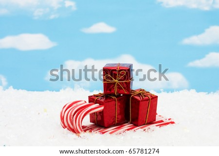 Candy canes making a sleigh with presents on them with a sky background, candy cane sleigh - stock photo