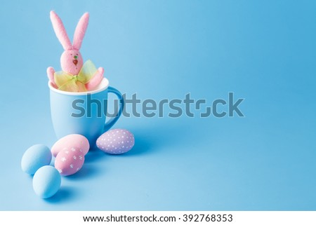 Candy color easter eggs with rabbit over mint - stock photo