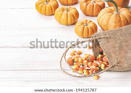 Candy Corn Spilling from Burlap Bag with mini pumpkins on Rustic White or Gray Wood Board Background with room or space for copy, text.  Horizontal, desaturated washed-out vintage instagram. - stock photo
