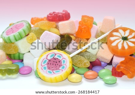 Candy, lollipop, colored smarties and gummy bears in foreground and blurred candy packages in pink background - stock photo