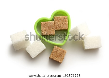 Cane and white sugar cubes in heart form - stock photo