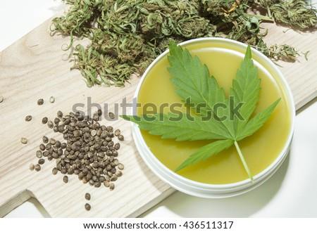 Cannabis healing ointment and marijuana leaf and seeds - stock photo