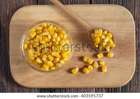 Canned corn grain in bowl on a kitchen board, top view - stock photo