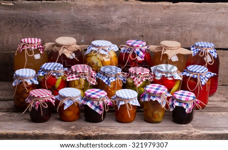 Canned food in the beautiful decorations on the old shelf. Glass jars close-up with fruits and vegetables on vintage background.  - stock photo
