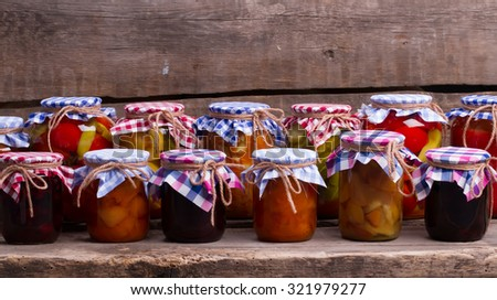 Canned fruits and vegetables in the cellar. Jars with fruit and vegetables standing on an old wooden shelf. - stock photo
