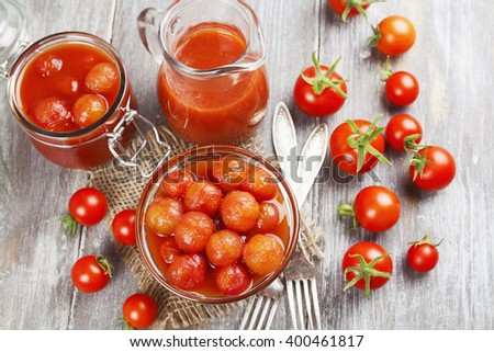 Canned tomatoes in tomato juice on a wooden table - stock photo